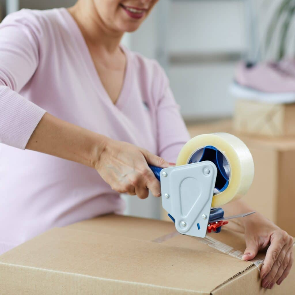 Contemporary vendor of online goods sealing package with adhesive tape